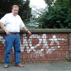 Jürgen Lüdemann vor Graffitis